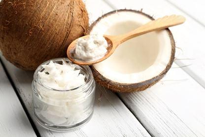 Aufgeschnittene Kokosnuss und Kokosöl auf Löffel